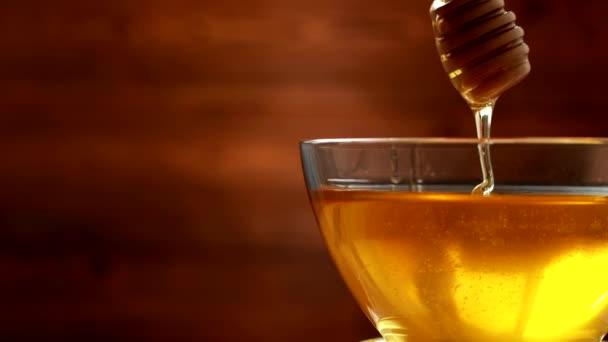 Lahodný a zdravý med v misce teče dřevěnou tyčinkou pro med, kopírovací prostor, organické