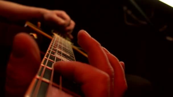 Egy férfi játszik a gitár ujjak és húrok közelről. Többszínű színpadi világítás, háttér, lassított felvétel