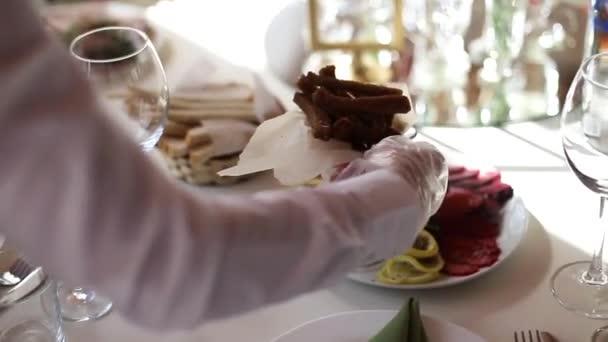 Číšník servíruje jídla na slavnostním stole. Krásná jídla na banketovém stole, zázemí