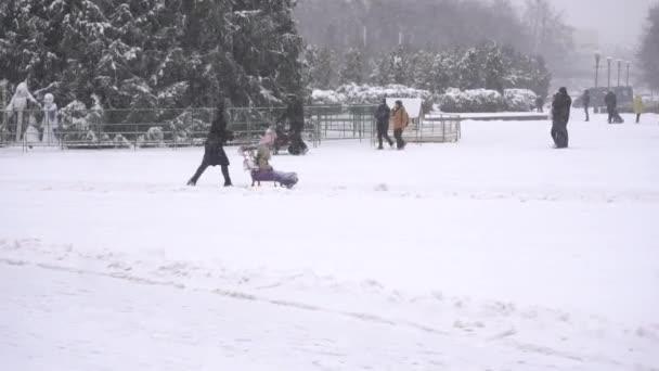Lidé hrají sněhové koule a procházka v zimním městě ve sněhu, zpomalení. Outdoor