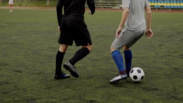 A focista cselez a védők lábai között. Labdarúgás váratlan manőver, megtévesztő mozdulat. Amatőr játék egy kis stadionban. Edzés tréning. Csapatbarát meccs. Sport