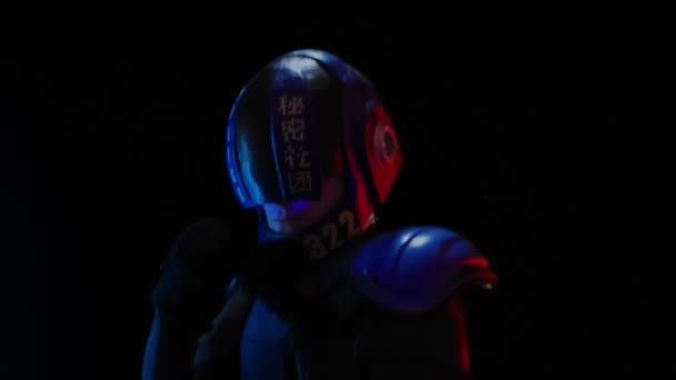 Cyberpunk jövőbeli koncepció. A rendőr boksz pózban áll, integet, és behúzott egyet a sötétben. Félember robot készen áll a harcra. A bionikus kiborg a kamerába néz. Sci-fi jelenet, sci-fi