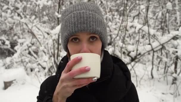 Nő inni bögre forró gőzölgő tea kezében téli erdőben hó