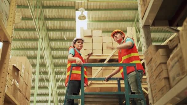 Az ázsiai munkások lépcsőt használnak, hogy raktárakat rendezzenek a felső emeleten..