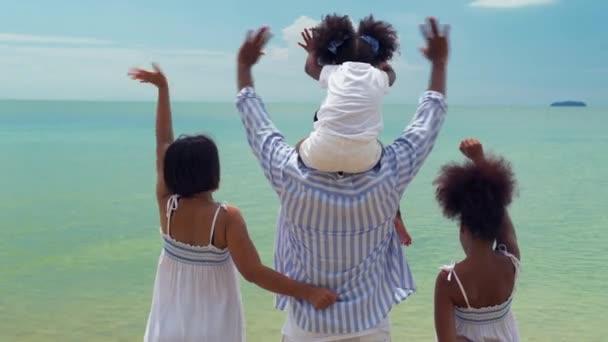 Afroamerikanische Familien winken am Strand.