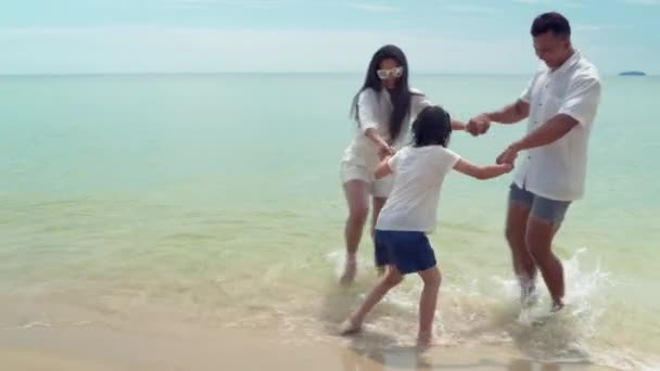 An Asian family playing on the beach on a summer weekend.
