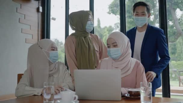 Geschäftstreffen von Islamisten, die eine Maske gegen die Epidemie COVID-19 tragen und ihren Glückwünschen applaudieren, nachdem ein Vorgesetzter den Erfolg der Veranstaltung verkündet hat.