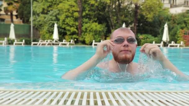mladý muž vousy objeví v hotelovém bazénu v plaveckých brýlích