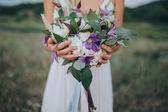 Fotografie Dívka v bílých šatech drží kytici