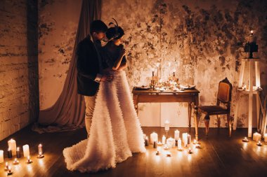 Bride and groom standing among candles