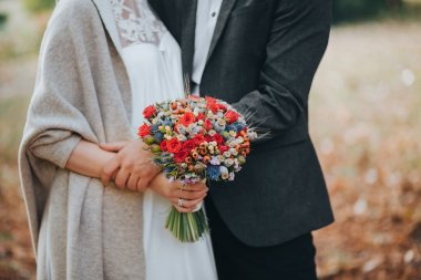 Groom and bride holding wedding bouquet