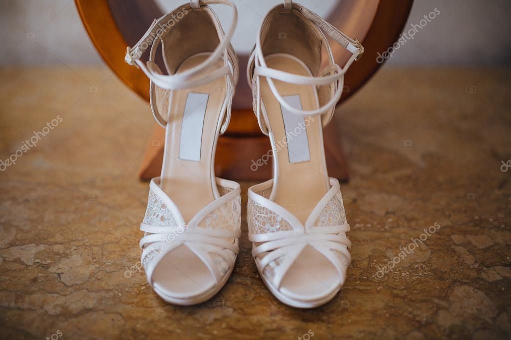 a3a5e81ce3ce67 Весілля. взуття нареченої. Ілюстрації. Кукурудза. Білі туфлі нареченої  стоячи під настільну лампу на дерев'яний стіл– стокове зображення