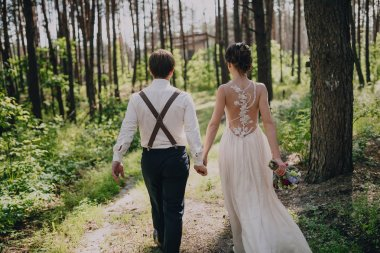 The bride and groom go through the forest hand in hand