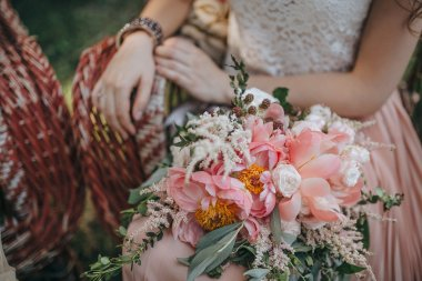 girl sitting in a wicker garden chair and holding a bouquet of pink and white peonies and green