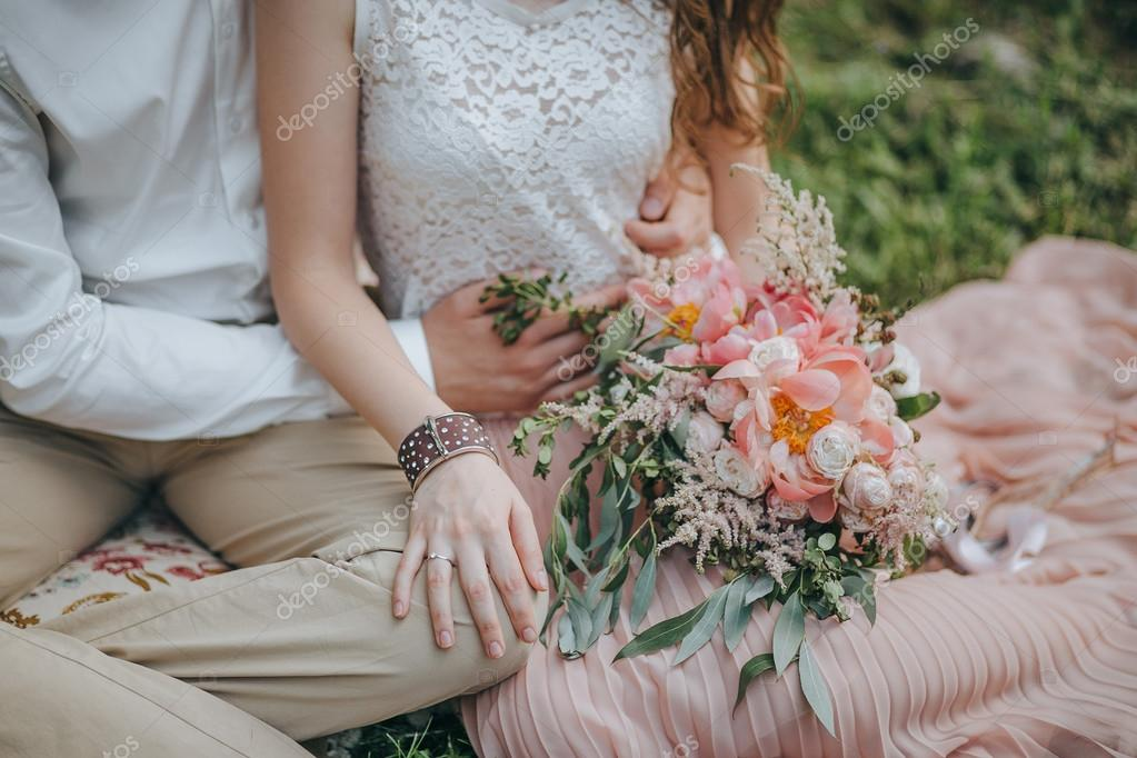 couple sitting on the grass and holding a bouquet of pink and white peonies and green