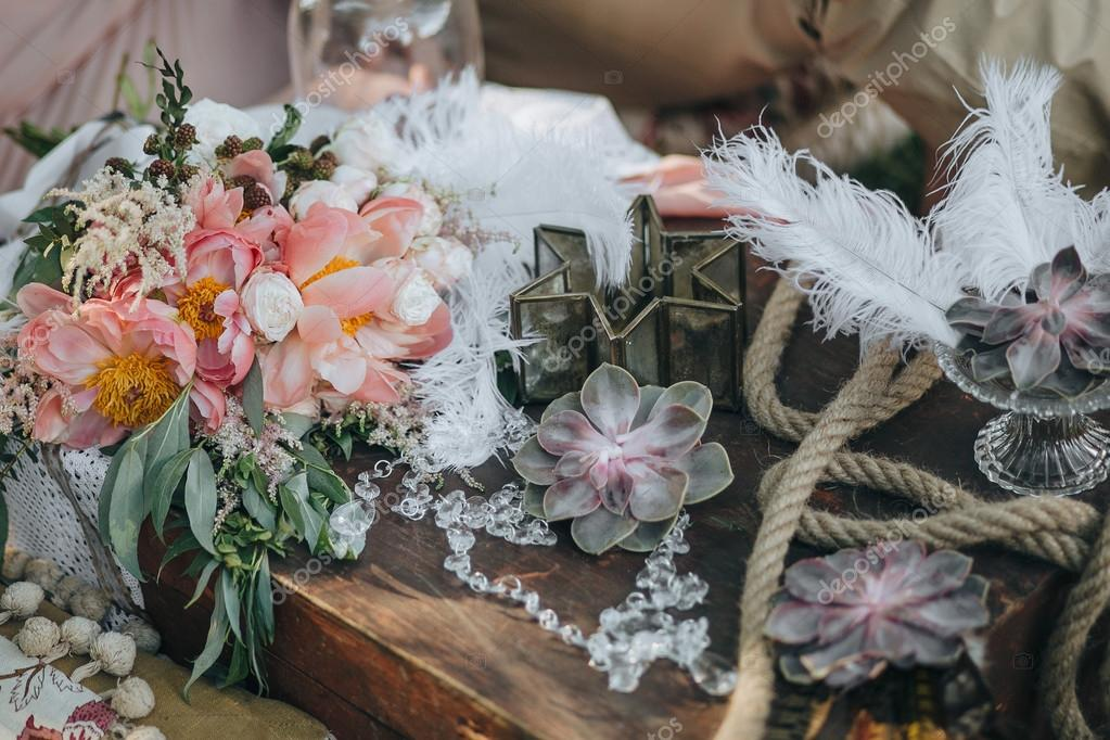 bouquet of pink and white peonies and greenery lies in an area decorated with succulents, feathers and vintage decor