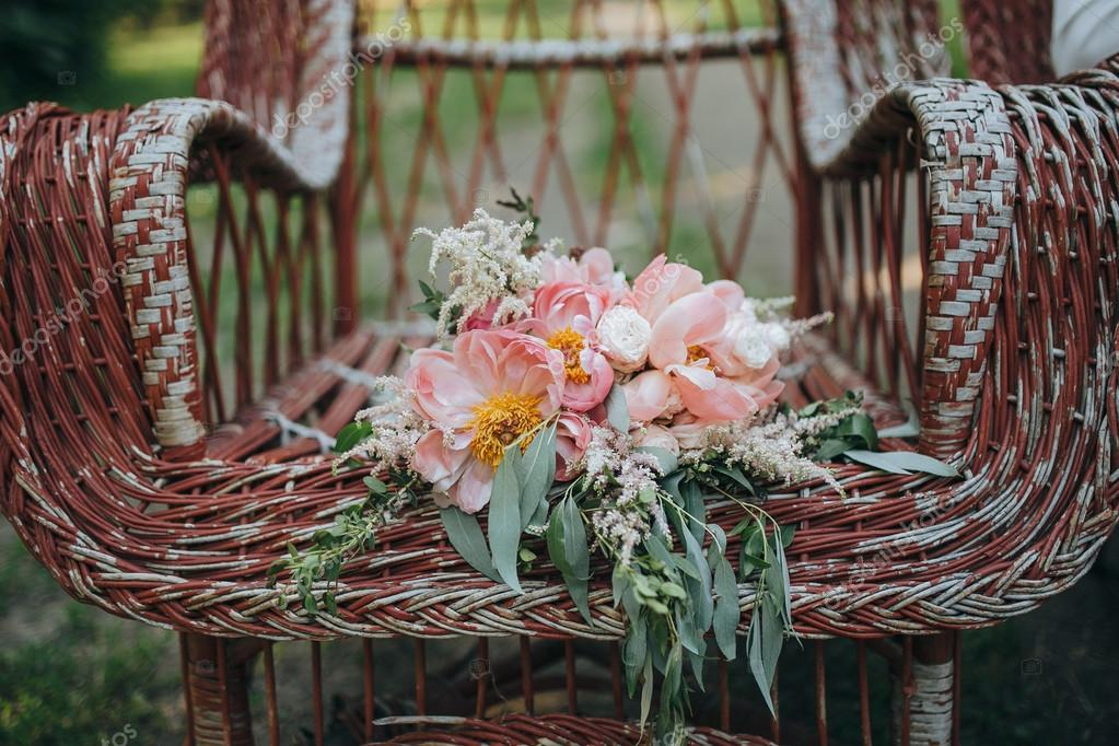 bouquet of pink and white peonies and green is in a vintage garden chairs on the background of green garden