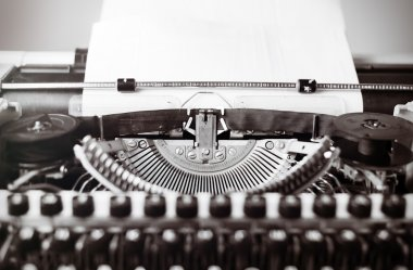 Old typewriter on wooden table. Vintage style tinted photo.