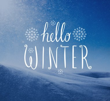 Photo of snowstorm in sunny day with Hello Winter lettering.