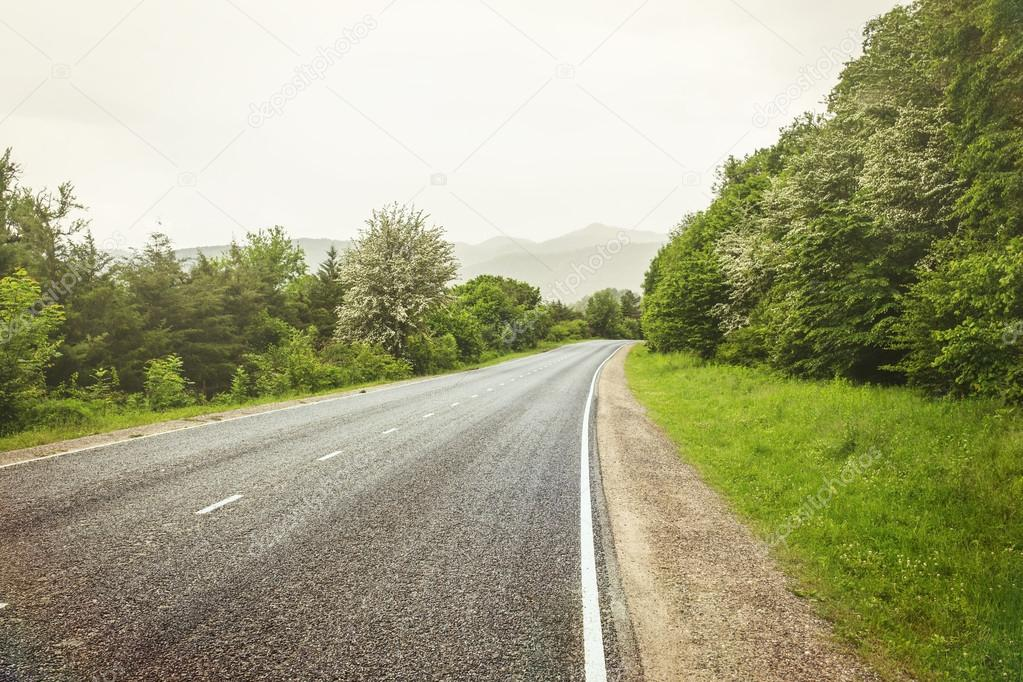 Empty asphalt road in mountains, tinted photo with some filters