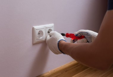 Electrician installing a wall power socket, close up photo