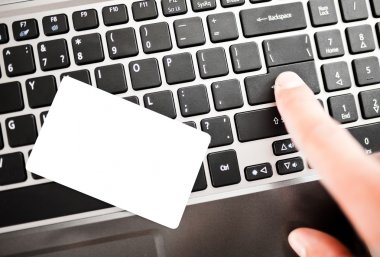 Closeup of a man shopping online using laptop with credit card.