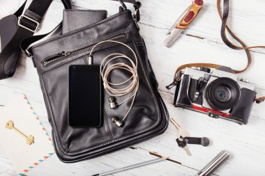Objects on wooden background: leather bag, camera, smartphone, k