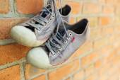 Fotografia Old worn sneakers on brick wall
