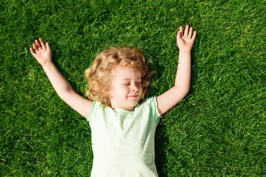 Dreaming adorable little girl lying on grass, top view
