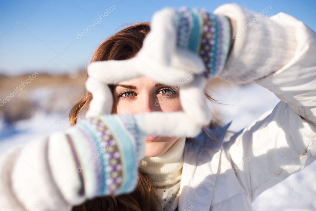 Chica guapa que se divierten al aire libre, lo marco con las manos ...
