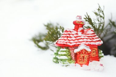 Christmas house toy with decoration in snow at winter day. Close