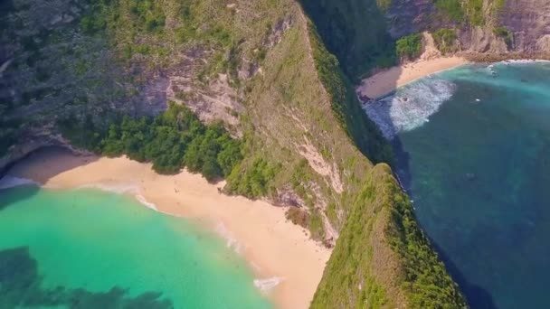 epic pull back drone shot on unique and exotic tropical desert beach in the island of Nusa Penida - Bali in Indonesia revealing rock cliff on turquoise sea water