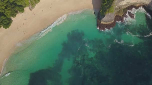 beautiful aerial drone shot on unique and exotic tropical paradise beach in the island of Nusa Penida - Bali in Indonesia new to cliff covered in green vegetation