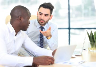 Image of two young businessmen interacting at meeting