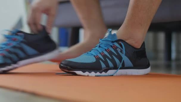Mann bindet seine Schnürsenkel im Schlafzimmer, bereitet sich auf das Training vor, Innenraum-Trainingskonzept, Nahaufnahme