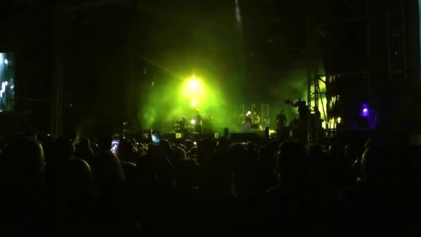 egy utcai koncerten fényes megvilágítással, az emberek jól érzik magukat