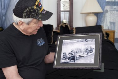 Vietnam war veteran looks at old war photo of himself.