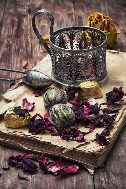 tea accessories amid frayed books