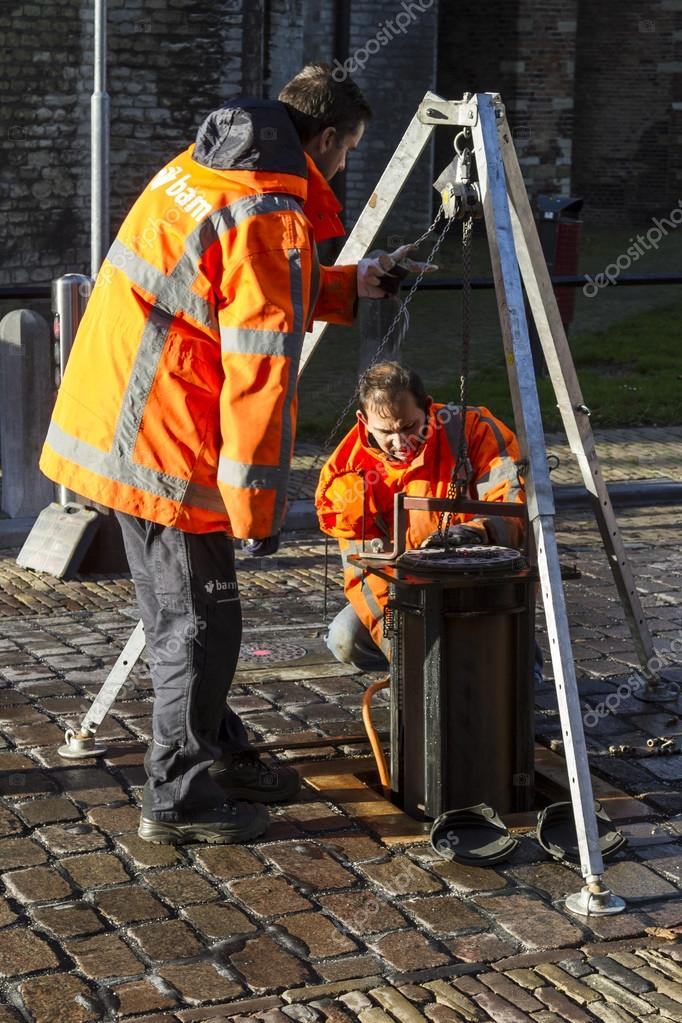 Technical workers repairing automatic bollards set in a cobble paved street