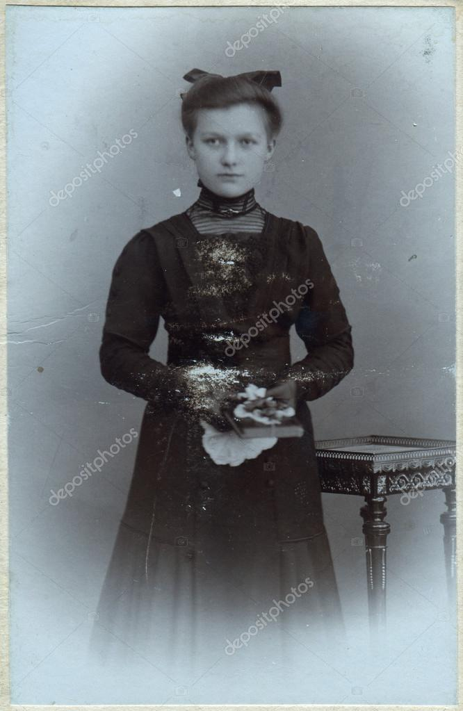 A Vintage Portrait Of A Young Woman Standing Near A Table