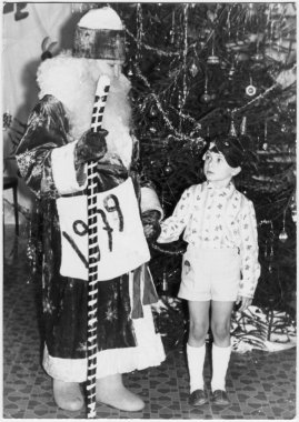 Traditional children's party, New Year party in the kindergarten. Celebrated on the eve of the new year. Father Frost with a boy