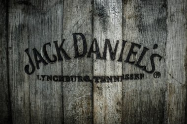 Burned logo of the famous Jack Daniels whiskey at the old wooden barrel.