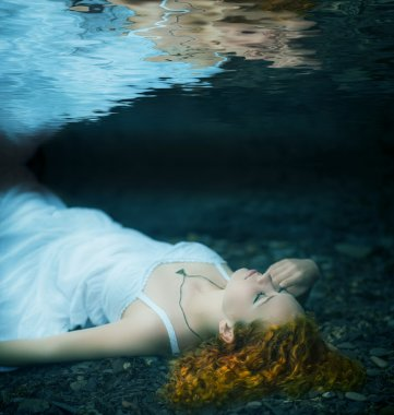Young woman lying underwater.