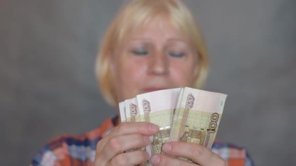 Traurige Frau beim Geldzählen.