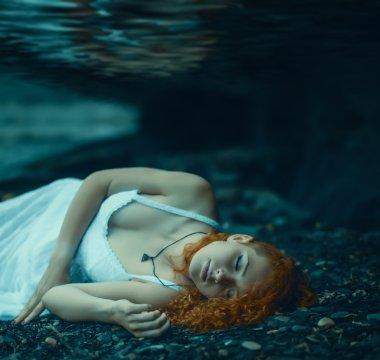 Woman lying underwater.