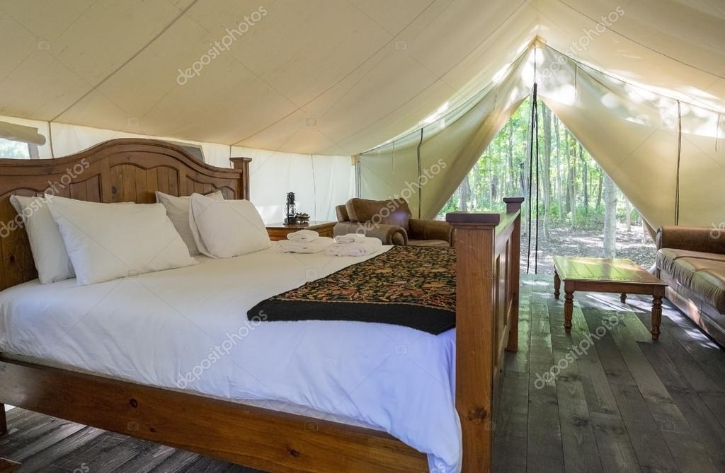 interior of a large luxury white canvas tent in the woods stock photo