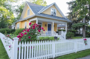 Yellow House with Pink Rose Bush in Front
