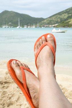 Woman Wearing Orange Flip Flops on a Beach