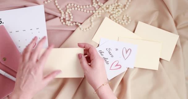 Woman hands putting save the date card in the envelope. Wedding planning, invitation concept