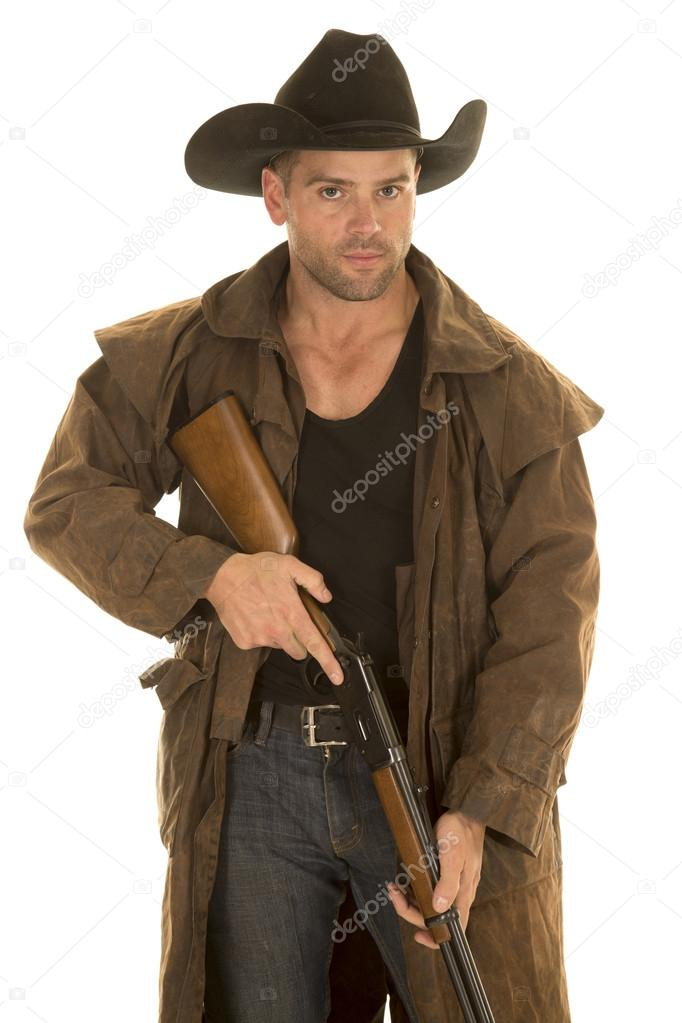 cowboy in black hat and duster hold rifle look stock photo